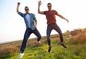 Portrait Of Two Friends Jumping In Field.