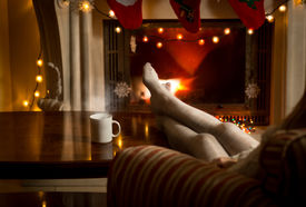 foto of stocking-foot  - Beautiful female legs in woolen stockings warming up at fireplace - JPG