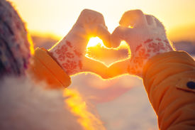 stock photo of february  - Woman hands in winter gloves Heart symbol shaped Lifestyle and Feelings concept with sunset light nature on background - JPG