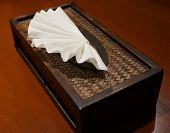 picture of tissue box  - White tissue paper was nicely decorated in tissue box on wooden table - JPG