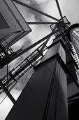 stock photo of elevators  - Grain elevator architecture with leading lines against the sky in black and white - JPG