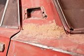 stock photo of putty  - Layer of putty on old rusty car - JPG