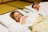 image of futon  - Kids sleeping on futons at traditional Japanese style room - JPG