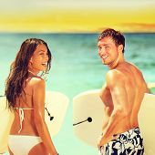 stock photo of woman couple  - Surfers on beach having fun in summer - JPG
