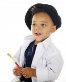 pic of french beret  - Closeup portrait of an adorable preschool artist holding a paint brush while wearing a white smock and French beret - JPG