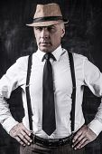 pic of suspenders  - Confident senior man in hat and suspenders looking at camera and holding hands on hip while standing against dark background - JPG