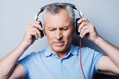 foto of frustrated  - Portrait of frustrated senior man in headphones listening to music keeping eyes closed while standing against grey background - JPG