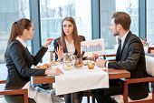 stock photo of buffet lunch  - Fresh idea on doing business. Business colleagues discuss data displayed on chart while sitting at the lunch table ** Note: Visible grain at 100%, best at smaller sizes - JPG