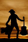 foto of cowgirls  - A silhouette of a cowgirl with her guitar in one hand and her saddle in her other hand - JPG