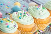 stock photo of easter candy  - Pastel Easter cupcakes with candy and sprinkles on blue wooden vintage background shallow depth of field - JPG