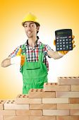 pic of overspending  - Expensive construction concept with builder and calculator - JPG