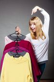 picture of clothes hanger  - Retail and sale. Blonde girl fashionable woman showing clothes. Client customer pointing with finger hangers with colorful clothing gray background ** Note: Soft Focus at 100%, best at smaller sizes - JPG