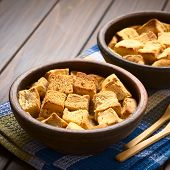 picture of dice  - Two rustic bowls of bread pudding made of diced stale bread milk egg cinnamon sugar and butter photographed with natural light  - JPG