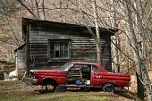 pic of forlorn  - an abandoned red car in front of an old building - JPG