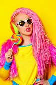 foto of dreadlock  - Attractive glamorous girl wearing ultra bright clothes and with pink dreadlocks eating lollipop - JPG