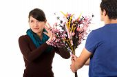 picture of she-male  - Hispanic couple fighting as man tries to give girlfriend flowers while she pushes them away with annoyed facial expression - JPG