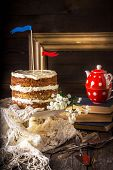 stock photo of teapot  - Naked Layer Cake teapot vintage tableware and books on wooden table - JPG