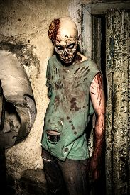 foto of doomsday  - Horrible scary zombie man on the ruins of an old house - JPG