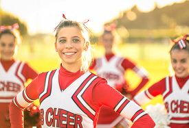 pic of pom poms  - Portrait of an happy young cheerleader in action outdoors  - JPG
