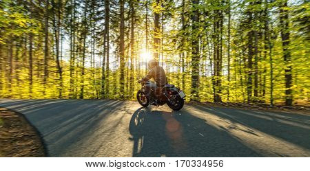 Motorcycle driver driving in forest