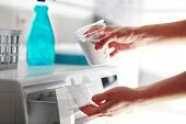 hands of woman that fills detergent in the washing machine  poster