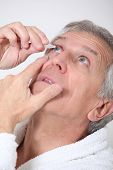 Senior man putting eye drops