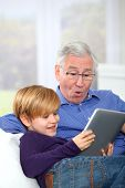 picture of grandpa  - Grandpa with little boy using electronic tablet - JPG