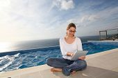 Woman using electronic tablet by swimming pool