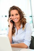 Smiling office worker talking on mobile phone