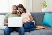 Young couple using a laptop while relaxing on a sofa in the living room poster