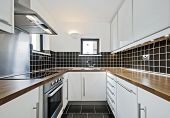 modern kitchen with black ceramic tiles and wooden worktop