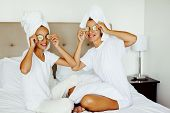 Mom and her 10 years old preteen daughter chilling in the bedroom and making clay facial mask. Mothe poster