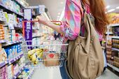 Close up view of woman doing grocery shopping with shopping basket at supermarket poster