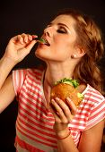 Woman eating sandwich. Girl with pleasure eats burger after diet. Female seductively eating a hambur poster