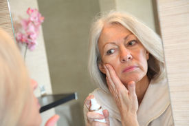 picture of beautiful senior woman  - Senior woman applying moisturizer on her face - JPG