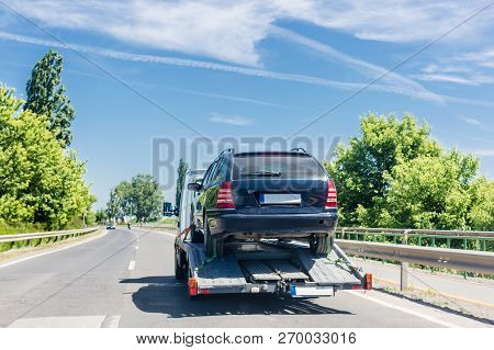 poster of Car Carrier Trailer With Car. Car Transported On Evacuation Tow Truck On Highway