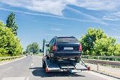 Car Carrier Trailer With Car. Car Transported On Evacuation Tow Truck On Highway poster