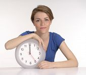 Young woman holding a clock on white background.