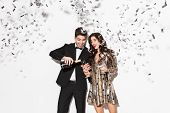 Cheerful young smartly dressed couple celebrating New Year party isolated over white background, dri poster
