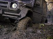 Wheel In Deep Rut Goes Through Mud And Leaves Trail. Dangerous Expedition Concept. Dirty Offroad Tir poster