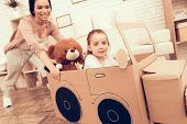Rolls Girl In Cardboard Car. Child Development. Mom And Daughter Play. Happy Mom And Child Build Car poster