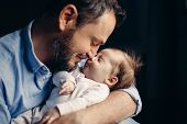 Closeup Portrait Of Middle Age Bearded Caucasian Father Hugging And Kissing Newborn Baby. Male Man P poster