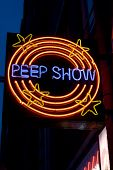 stock photo of brothel  - Lighted peepshow sign in Amsterdam against a blue night sky - JPG
