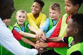 Junior football team stacking hands before a match poster