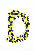The letter D alphabet made of medical capsules