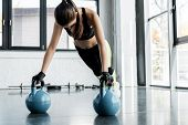 Strong Sportswoman In Weightlifting Gloves Doing Plank Exercise On Kettlebells At Gym poster