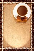 cup of coffee standing on sackcloth, and around the grains of roasted coffee