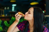 Beautiful Brunette Girl In T-shirt Eating Pizza At Restaurant. A Pretty Girl Feels Happy And Enjoys  poster