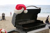 Santa Claus hat on a Barbecue grill. Outside barbecue grill at the beach with a Santa Hat. poster