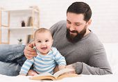 Young Man Babysitting. Bearded Father Reading Book To His Adorable Baby Son poster